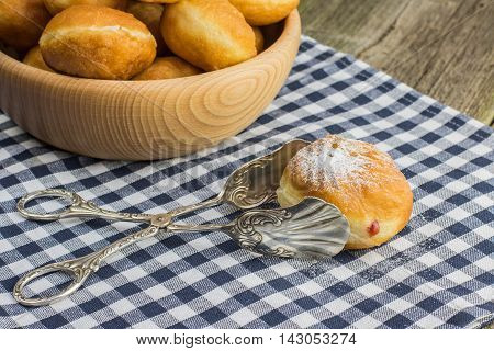 Fried Berliner (doughnut) with strawberry jam in pastry tongs