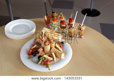 Mini Canape with meat and vegetables in glass cups, stand on the buffet. On the plate canape of prawn and chicken sandwiches