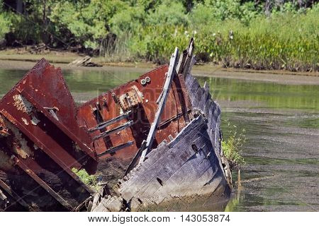 A wrecked wooden boat stuck in the shallow water