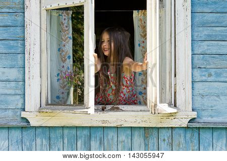 Happy smiling little girl opening window of rustic house in the early sunny morning