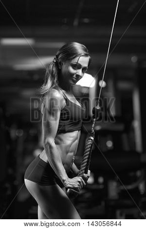 Black and white photo. Fitness woman in the gym. Young woman doing fitness exercises in the gym. Perfect physique athletic young woman, perfect abs, shoulders and biceps.