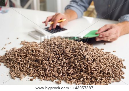 Hands on calculator calculationg household heating costs. Wooden pellets biomass effective environmentally friendly and economical heating sustainable and renewable energy.