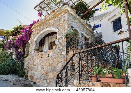 Traditional Greek stone house with  purple bougainvillea flowers on Crete island