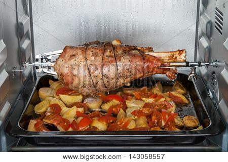 Leg of turkey baked with potatoes and tomatoes in an electric oven