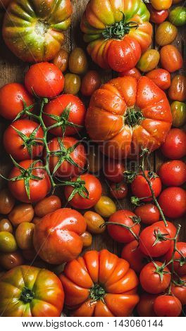 Colorful tomatoes of different sizes and kinds, top view, vertical