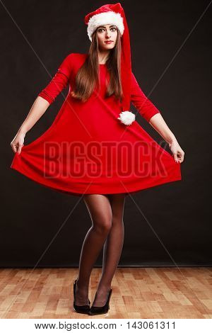 Christmas time. Young woman wearing santa claus hat red dress on black background. Studio shot.