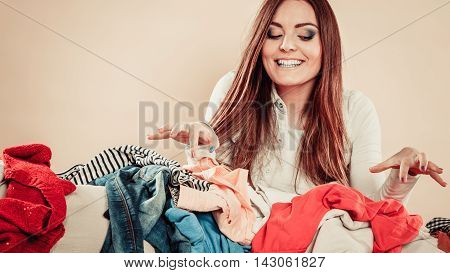 Woman Behind Sofa Full Of Clothes With Lifted Hands.