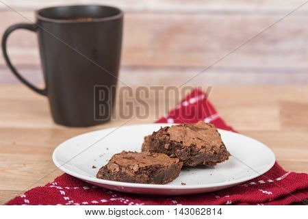 Homemade brownies with black cup in background