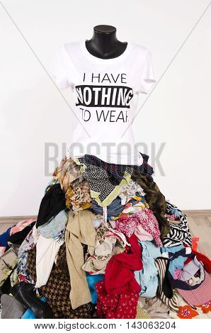 Big pile of clothes thrown on the ground with a t-shirt saying nothing to wear. Untidy cluttered wardrobe with colorful clothes and accessories many clothes and nothing to wear top on a mannequin.