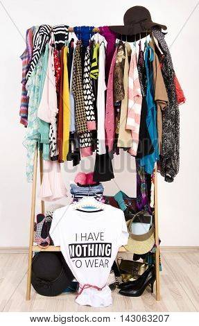Many clothes on the rack with a t-shirt saying nothing to wear. Close up on a cluttered wardrobe with colorful clothes and accessories many clothes and nothing to wear.
