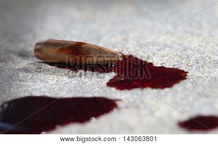Rifle bullet on concrete that has blood around