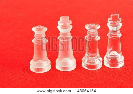 Both the king and queen pieces that is used in a chess game displayed on a red background