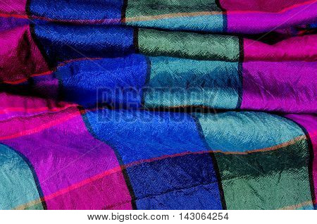 Crumpled checked fabric. Green, green and magenta plaid print as background. Colored square pattern. Tartan pattern.