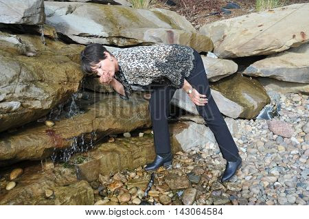 Mature female beauty drinking water from a fountain of youth outdoors.