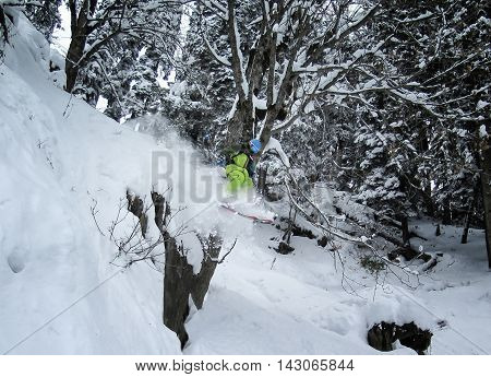 Mountain freeride skier jumping off cliff in deep snow on pine forest in Himalayas