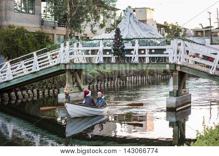 Venice, USA - December 25, 2015: Couple in boat with red santa hats under romantic canal bridge with snow mountain and christmas tree decoration