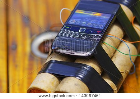 cellphone tied to a set of explosives laying on the ground.