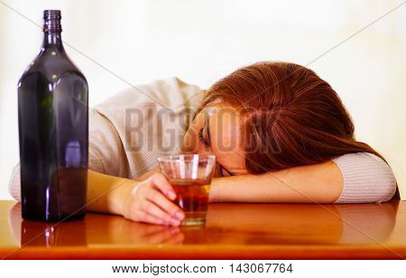 Attractive woman wearing white sweater sitting by bar counter lying over desk next to glass and bottle, drunk depressed facial expression, alcoholic concept.