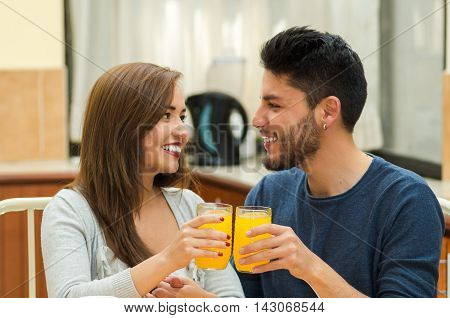 Young charming couple seated by breakfast table smiling to camera cheering with glasses, fruits, juice and coffee placed in front, hostel environment.