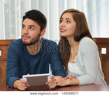 Young charming couple seated by table watching tablet screen while embracing, bot happy and smiling, hostel concept.