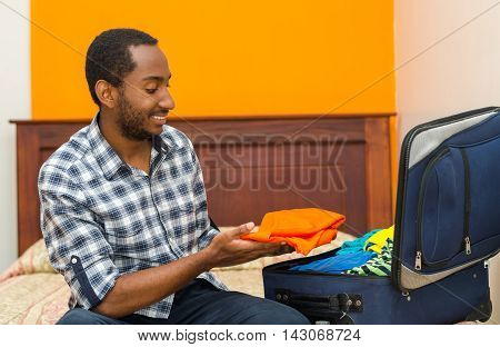 Handsome young man sitting on bed packing suitcase and smiling, hostel guest concept.