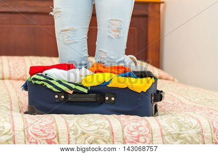 Open suitcase with clothes inside lying on bed, womans legs in background, hostel guest concept.