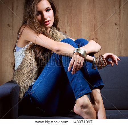 Portrait of elegant woman sitting on black sofa wearing a blue jeans and fur vest