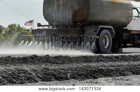 Water truck spraying water on roadway in preparation for construction