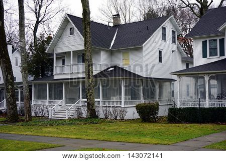 An elegant Victorian home, with a wraparound front porch and a balcony, on Fifth Avenue in Wequetonsing, Michigan.