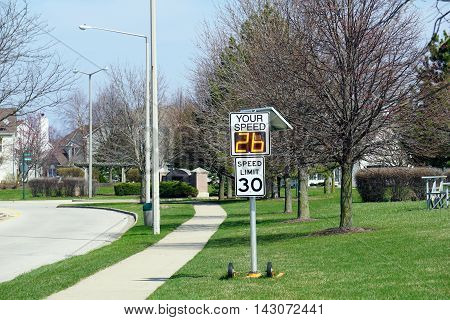 JOLIET, ILLINOIS / UNITED STATES - MARCH 26, 2016: A radar speed sign indicates that a vehicle is approaching at 26 miles per hour.