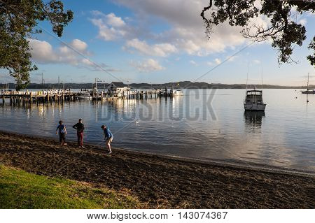 Russell New Zealand (NZ) - 13 August 2016. Children skimming stones on the beach at Russell in the Bay of Islands Northland.