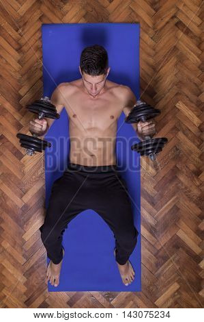 Young man abs dumbbell elevated view rear