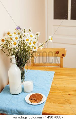 Simply stylish wooden kitchen with bottle of milk and glass on table, summer flowers camomile, healthy food moring concept breakfast