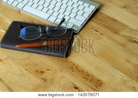 On business office work space computer keyboard brown note book eye glasses on wood desk