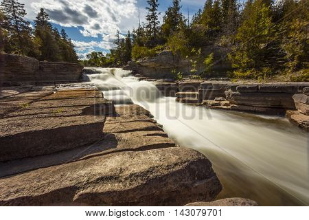 Daytime view of Fouth Chute cascade in Eganville Ontario Canada during a sunny day