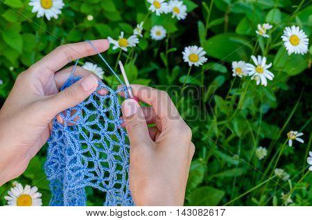 Female Hands Crochet Blue Cotton Yarn Openwork Fabric On A Background Of Green Grass