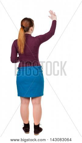 Back view of beautiful woman welcomes. Young teenager girl in jeans hand waving from. Rear view  people collection.  backside view of person.  Isolated over white background. Red-haired girl waving
