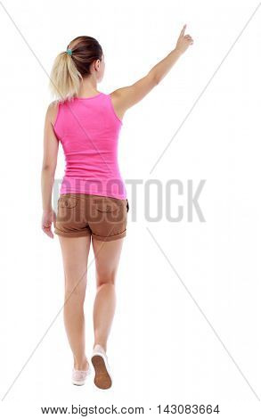 back view of pointing walking  woman. going girl pointing.  backside view of person.  Rear view people collection. Isolated over white background. Sport blond in brown shorts goes back frame pointing