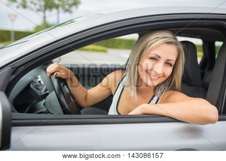 Woman driving a car - female driver at a wheel of a modern car, looking happy, smiling with a relaxed smile (shallow DOF; color toned image)