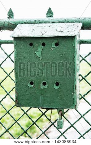 Old green metallic mailbox on the fence. Mail delivery. Retro object. Vertical composition.
