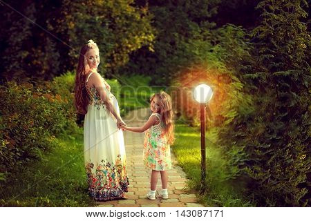Beautiful pregnant woman in the summer is walking with my daughter in a magical forest stopped on the path and turned around holding hands. The light of a lantern. Mom and girl.