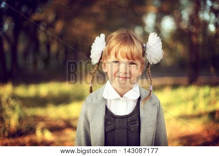Beautiful girl schoolgirl with bows and smiles looking at the camera