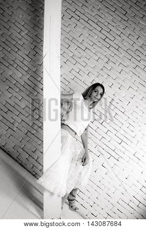 Girl sit on stairs on brick wall baclground