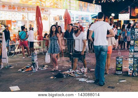 SUNNY BEACH BULGARIA - AUGUST 29 2015: Night view of Sunny Beach with people walk along the central street covered with garbage.