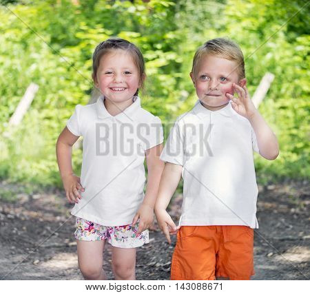 Little twins brother and sister in a park on sunny day