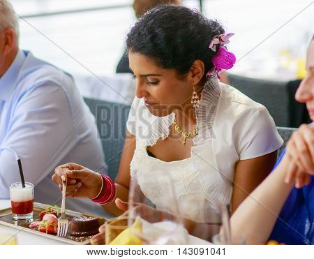 Beautiful happy indian bride eating on wedding dinner