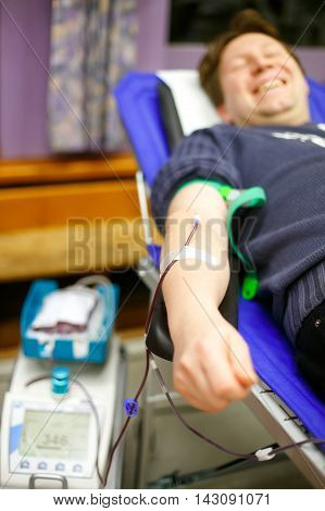 Young happy man donating his blood in Europe