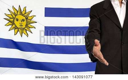 Businessman with an open hand waiting for a handshake concept for business with the Uruguay flag in the background