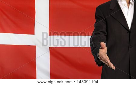 Businessman with an open hand waiting for a handshake concept for business with the Denmark flag in the background