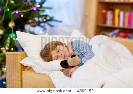 Adorable blond child sleeping with teddy bear under Christmas tree and dreaming of Santa at home, indoors. Happy kid boy waiting for gifts.